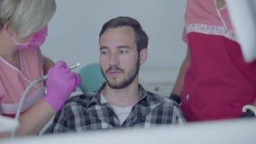 Retrato de un hombre asustado joven en la oficina del dentista Manos del doctor y de la enfermera que sostienen los hombros del p almacen de metraje de vídeo