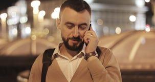 Retrato de un hombre atractivo con una barba que habla en su teléfono móvil almacen de video
