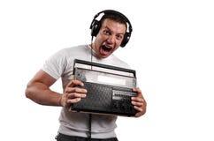 Retrato de un hombre atractivo de griterío con la radio vieja del vintage, aislante Fotos de archivo