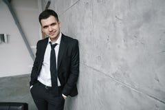 Retrato de un hombre atractivo joven en una chaqueta negra y del lazo contra una pared gris en el estilo del desván Fotografía de archivo libre de regalías
