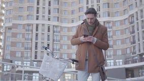 Retrato de un hombre atractivo que mecanografía en una célula mientras que se coloca con una bicicleta contra la perspectiva de a almacen de video