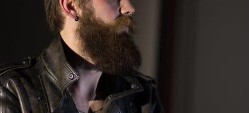 Retrato de un hombre barbudo de empollamiento en una chaqueta de cuero imagen de archivo libre de regalías