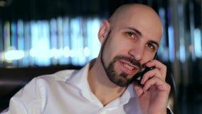 Retrato de un hombre barbudo feliz que habla en el teléfono almacen de metraje de vídeo