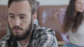 Retrato de un hombre barbudo ofendido que se sienta en el primero plano mientras que su esposa feliz que intenta en una bufanda e almacen de video
