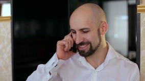Retrato de un hombre calvo que habla en el teléfono en un café almacen de video