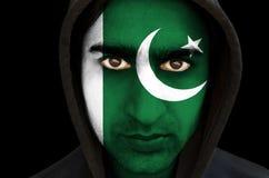 Retrato de un hombre con la pintura paquistaní de la cara de la bandera Imagen de archivo libre de regalías