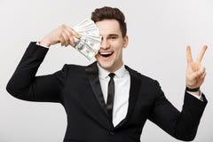 Retrato de un hombre confiado acertado que muestra el manojo de billetes de banco del dinero y que muestra la muestra del finger  Fotos de archivo