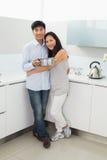 Retrato de un hombre de abarcamiento de la mujer joven en cocina Fotos de archivo