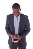 Retrato de un hombre de negocios afroamericano joven que usa un móvil Imagen de archivo