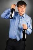 Retrato de un hombre de negocios borracho que sostiene dos botellas foto de archivo