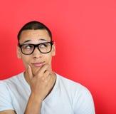 Retrato de un hombre de negocios divertido con los fingeres en la barbilla mientras que piense Fotografía de archivo