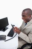 Retrato de un hombre de negocios enojado que contesta al teléfono mientras que usa Fotografía de archivo