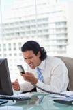 Retrato de un hombre de negocios enojado que grita en su microteléfono Fotos de archivo