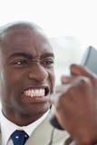 Retrato de un hombre de negocios enojado que mira su microteléfono del teléfono Imágenes de archivo libres de regalías
