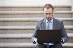 Retrato de un hombre de negocios que se sienta en las escaleras y que trabaja en l fotos de archivo libres de regalías