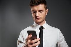 Retrato de un hombre de negocios serio joven usando el teléfono móvil Foto de archivo