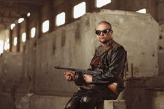 Retrato de un hombre del mundo posts-apocalíptico con la ametralladora y los vidrios negros en un edificio abandonado Fotografía de archivo