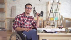 Retrato de un hombre discapacitado en una silla de ruedas con destornillador eléctrico a disposición metrajes