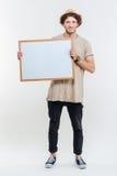 Retrato de un hombre elegante sonriente que lleva a cabo al tablero en blanco Fotos de archivo libres de regalías