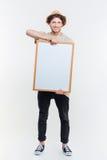 Retrato de un hombre elegante sonriente que lleva a cabo al tablero en blanco Fotografía de archivo