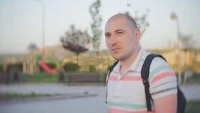 Retrato de un hombre en el fondo de un patio del ` s de los niños en una nueva zona urbana almacen de video