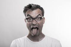 Retrato de un hombre en el repugnancia que empuja hacia fuera su lengua fotos de archivo libres de regalías