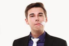 Retrato de un hombre en el traje que fuma un e-cigarrillo Foto de archivo libre de regalías