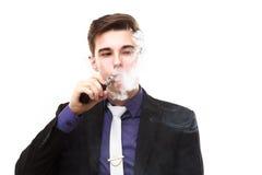 Retrato de un hombre en el traje que fuma un e-cigarrillo Fotos de archivo