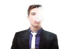 Retrato de un hombre en el traje que fuma un e-cigarrillo imagenes de archivo