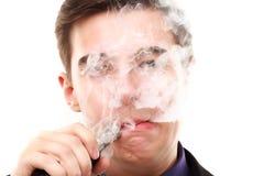 Retrato de un hombre en el traje que fuma un e-cigarrillo Foto de archivo