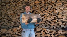 Retrato de un hombre en un sombrero de vaquero en un almacén que sostiene un manojo de leña almacen de metraje de vídeo