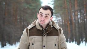 Retrato de un hombre en una chaqueta que aprueba algo cabeceando su cabeza El hombre se coloca en bosque del invierno almacen de metraje de vídeo