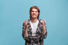 Retrato de un hombre enojado que mira la cámara aislada en un fondo azul Fotografía de archivo