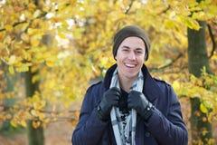 Retrato de un hombre feliz en sombrero de los guantes de la bufanda de la chaqueta que sonríe al aire libre en otoño Foto de archivo libre de regalías