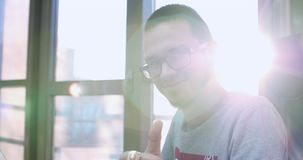Retrato de un hombre feliz joven en los vidrios, hombre de negocios, programador o comerciante, sentándose en la oficina con el o almacen de metraje de vídeo