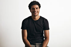 Retrato de un hombre hermoso en la sentada negra de la camiseta Imagen de archivo