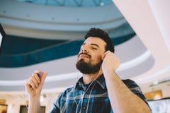 Retrato de un hombre hermoso joven con el Mp3 y de auriculares en urba foto de archivo