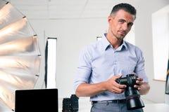 Retrato de un hombre hermoso que sostiene la cámara fotografía de archivo libre de regalías