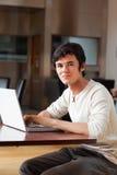 Retrato de un hombre hermoso que usa una computadora portátil Fotografía de archivo libre de regalías