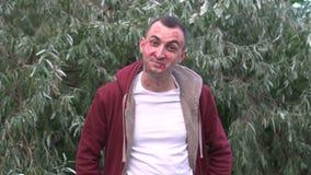 Retrato de un hombre joven al aire libre su cara entera se cubre con los rastros de besos Él es feliz almacen de video