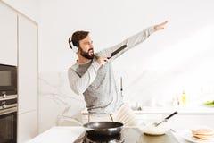 Retrato de un hombre joven alegre que cocina las crepes foto de archivo