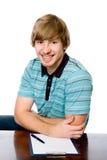 Retrato de un hombre joven alegre que se sienta detrás de un escritorio. Foto de archivo libre de regalías