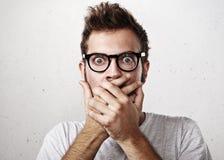 Retrato de un hombre joven chocado que cubre su boca con las manos Imagen de archivo libre de regalías