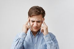 Retrato de un hombre joven con un dolor de cabeza terrible El individuo siente cómo el dolor pasa a través de su cerebro Distraen imagen de archivo libre de regalías