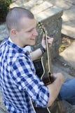 Retrato de un hombre joven con la guitarra al aire libre Fotografía de archivo