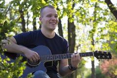 Retrato de un hombre joven con la guitarra en el parque imagen de archivo libre de regalías