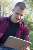 Retrato de un hombre joven con la tableta al aire libre Foto de archivo