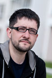 Retrato de un hombre joven con los vidrios que desgastan de la barba Imágenes de archivo libres de regalías