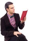 Retrato de un hombre joven con los vidrios que lee a BO Imagenes de archivo