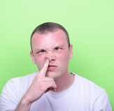 Retrato de un hombre joven con su finger en su nariz Foto de archivo libre de regalías
